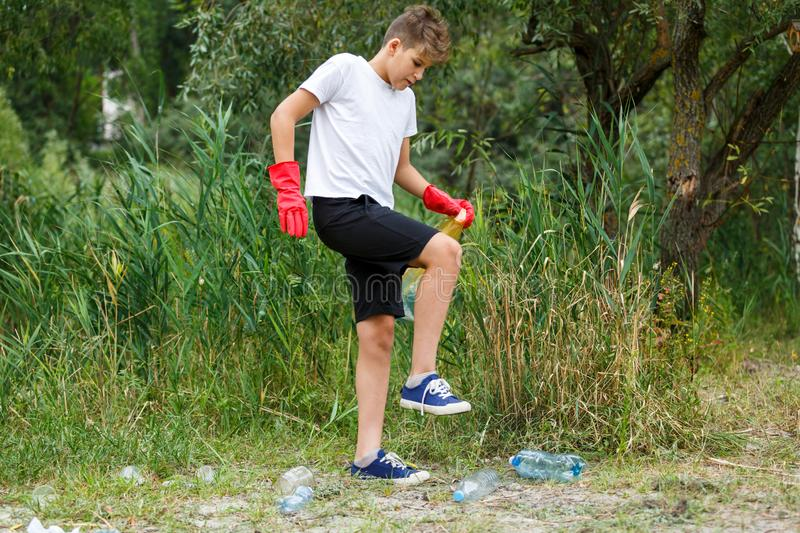 Boy in white t shirt in gloves collects garbage and plastic bottles into blue package on the beach. Young volunteer stock image