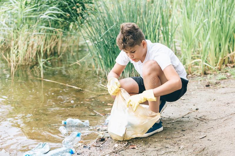 Boy in white t shirt in gloves collects garbage and plastic bottles into blue package on the beach. Young volunteer stock photo