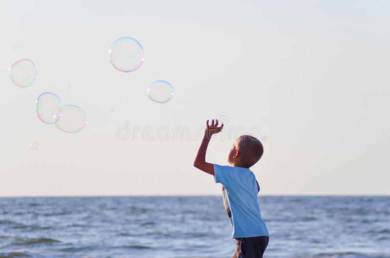 Boy In White T Shirt Playing Bubbles Near Body Of Water Under Grey Sky During Daytime Free Public Domain Cc0 Image