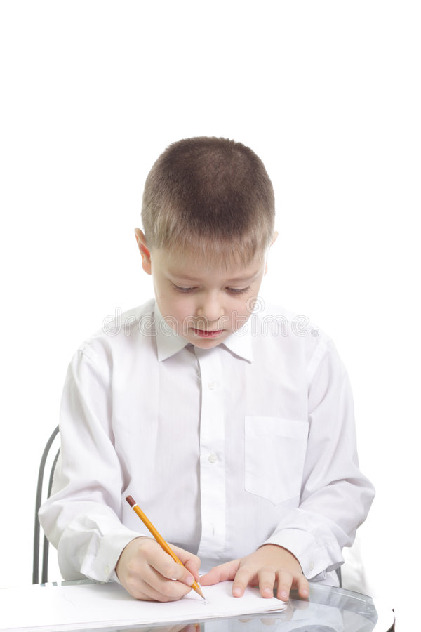 Boy in white writing at table royalty free stock photo
