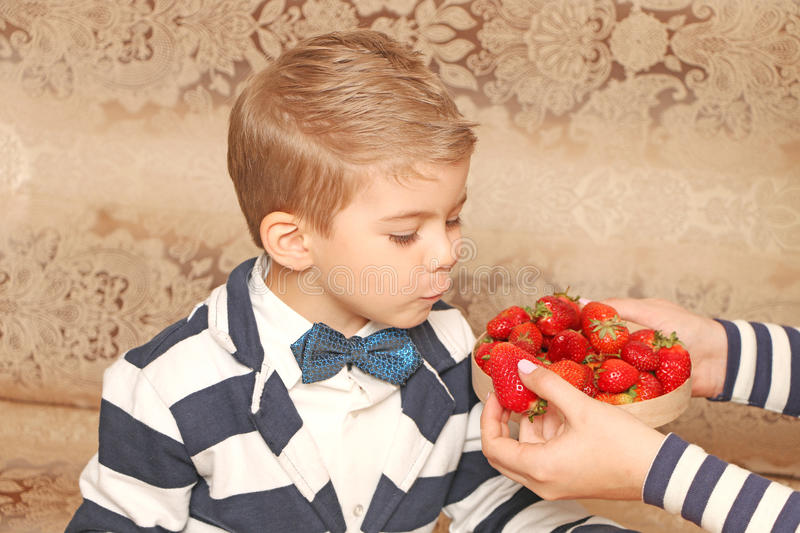 Boy who eating strawberries royalty free stock photography