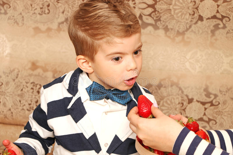 Boy who eating tasty strawberries. Good boy who eating tasty strawberries with smiling face stock photography