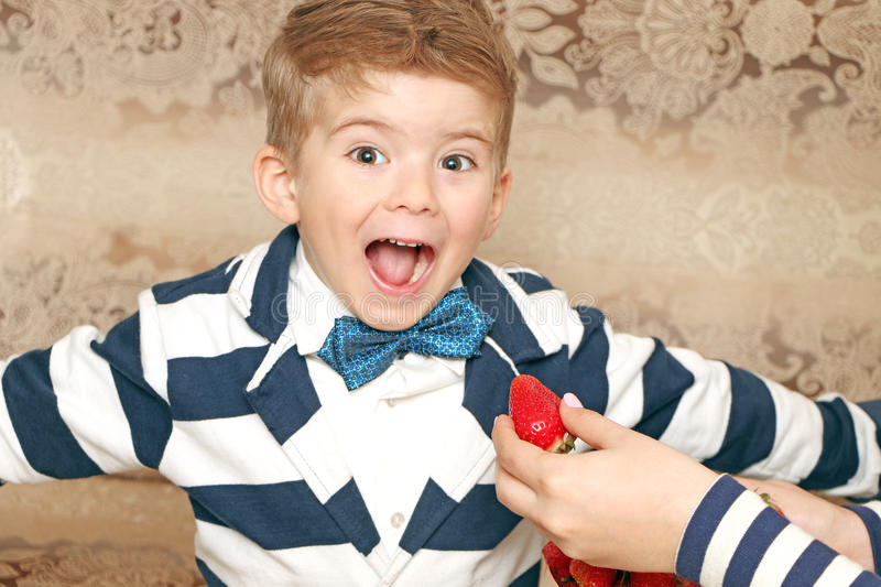 Boy who eating tasty strawberries. Good boy who eating tasty strawberries with smiling face royalty free stock photography