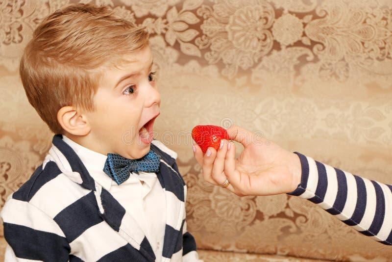 Boy who eating tasty strawberries. Good boy who eating tasty strawberries with smiling face royalty free stock photos