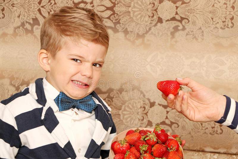 Boy who unhappy. Good boy who unhappy strawberries in a classic suit stock photography