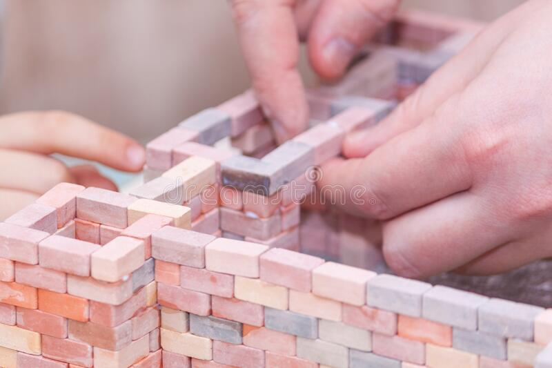 Boy wiht father building house from blocks and glue. Father with sun together play royalty free stock image