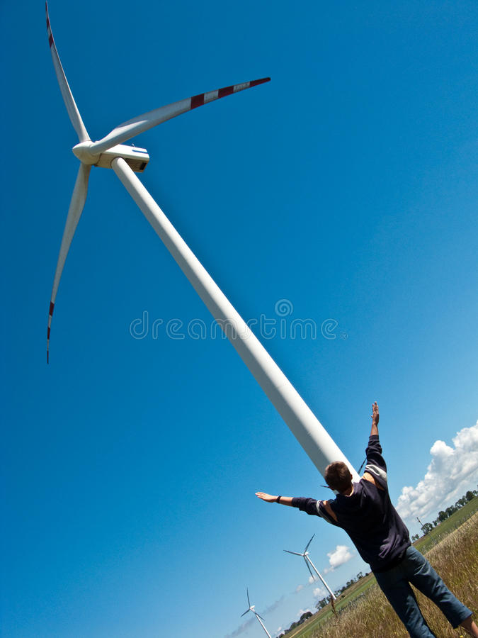 Boy and wind turbine. A teenage boy standing at the foot of a wind turbine in green field, raising his arms royalty free stock image