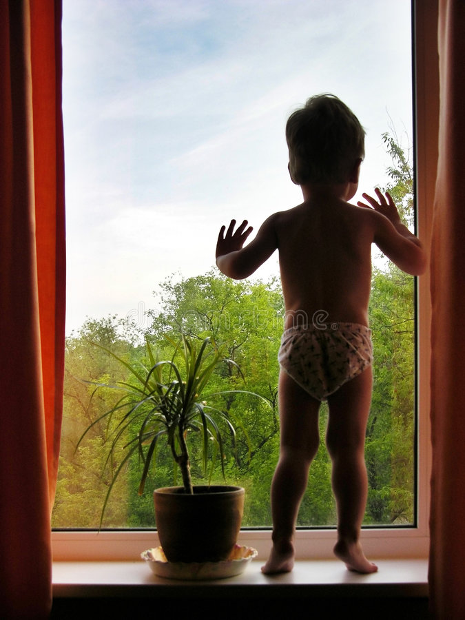 Boy and window stock photography
