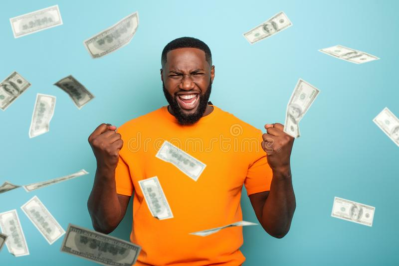 Boy wins money. Amazed and surprised expression face. Light blue background. Afro boy wins money. Amazed and surprised expression face. Light blue background royalty free stock images