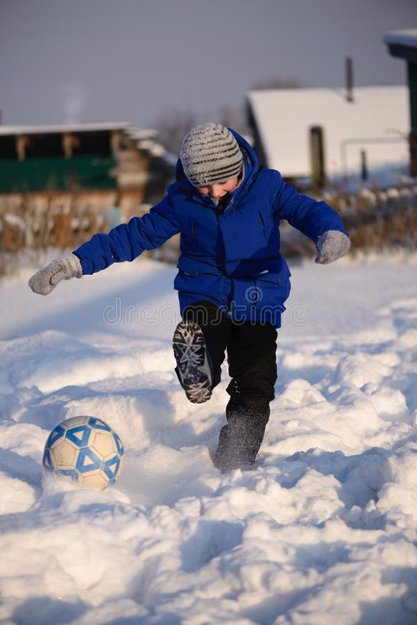 Schoolboy boy kicks the ball playing in winter football on the s. A boy in winter clothes playing football on the snow. Football player kicks the ball.The stock image