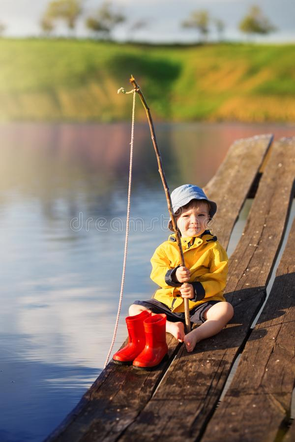 Boy on wooden dock with a fishing net stock photos