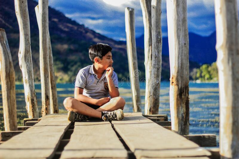 Boy on wooden pier royalty free stock image