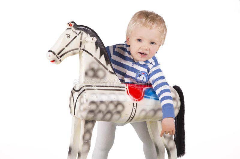 Boy and wooden rocking horse royalty free stock photography