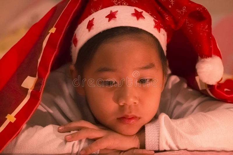 Boy wore a Christmas hat under a blanket, sadly and alone in the stock image