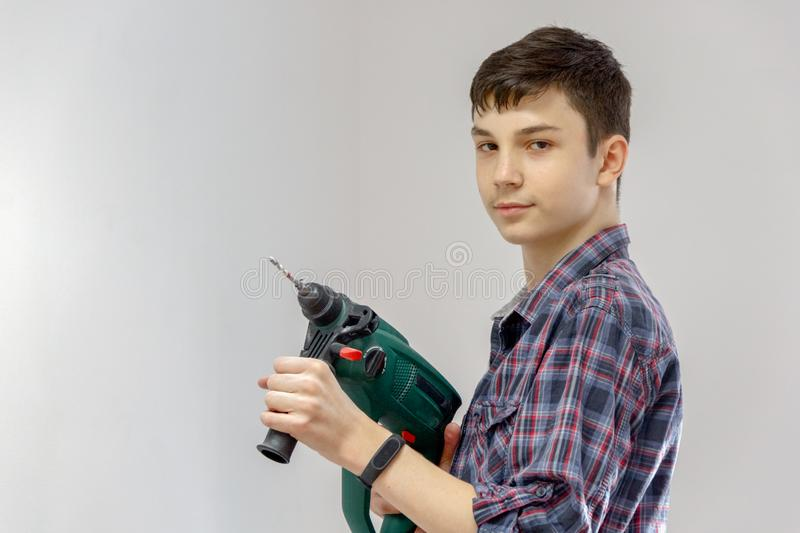 A teenager works as a builder, holding a drill or perforator. Concept of child labour, choice of profession royalty free stock images
