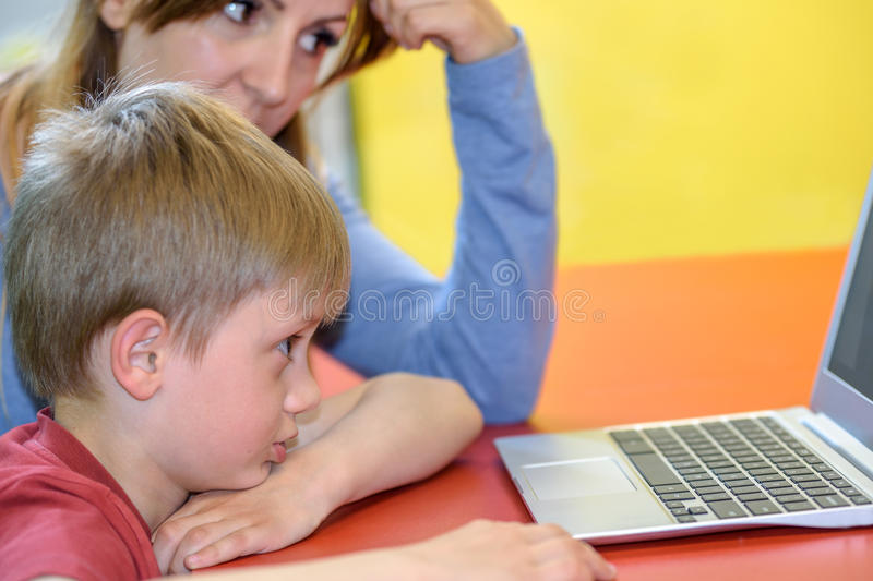 Boy works on a laptop with his mom. A little boy works or communicates on a laptop under the supervision of his mother stock image