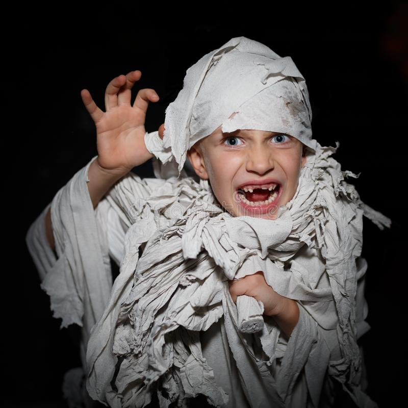 Boy wrapped in white bandages, like an Egyptian mummy, make faces on a black background royalty free stock images