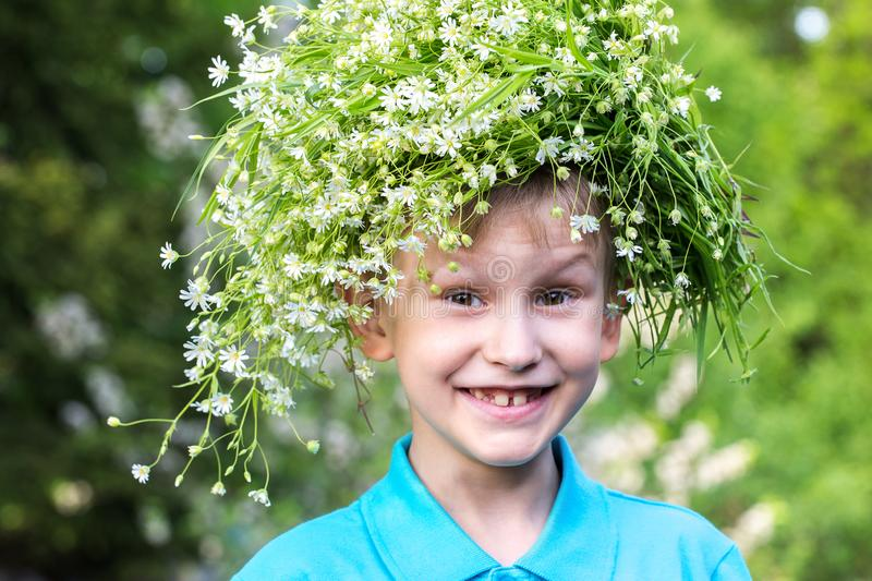 A boy with a wreath of wild flowers. Joy. European style smiling boy in blue polo with a wreath in the garden stock photos