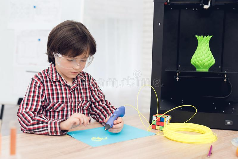 Boy writes by 3d pen during a lesson in class. royalty free stock photography