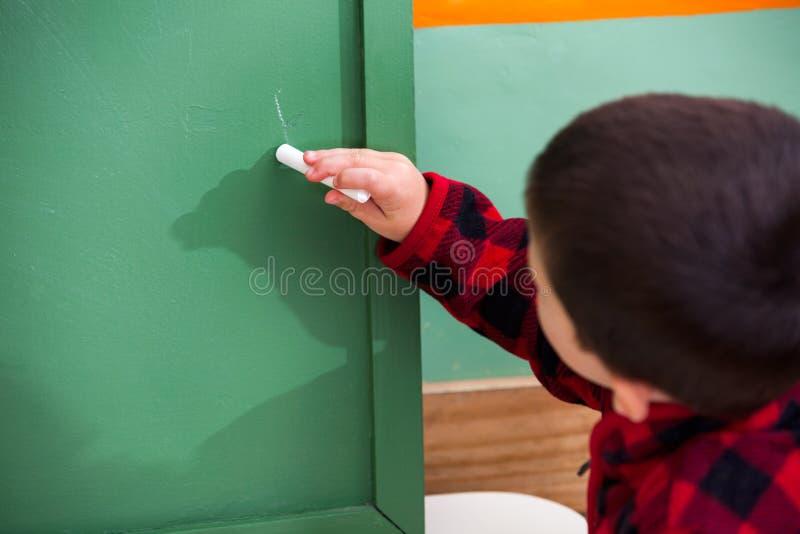 Boy Writing On Green Chalkboard In Preschool