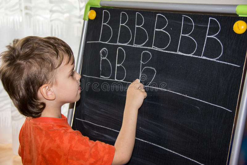 Boy writing letters learning procces son smart child stock image