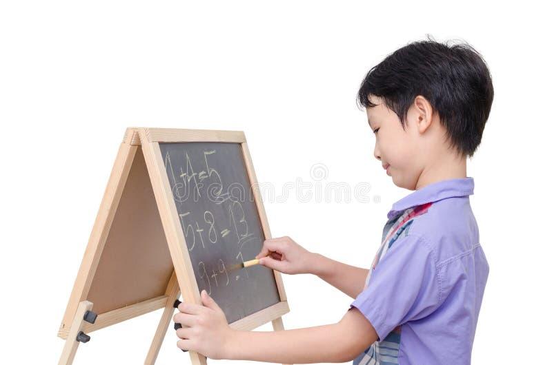 Boy writing math answer on chalkboard. Young asian boy writing math answer on chalkboard stock photos