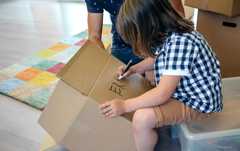 Boy writing in a moving box stock photography