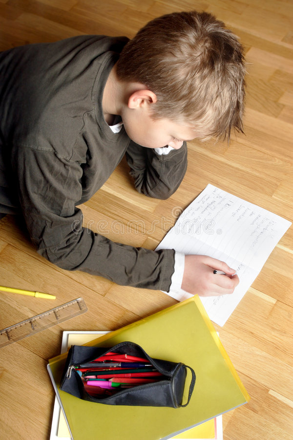Boy writing on paper, lying on the ground royalty free stock images