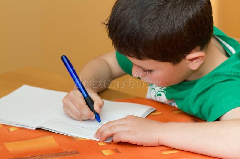 Boy writting homework from school in workbook. Small school boy writting homework from school in workbook royalty free stock images