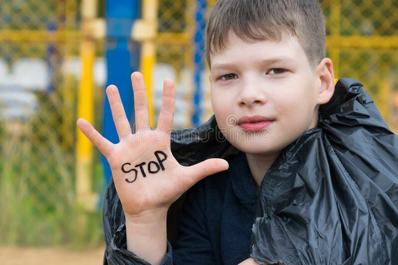 The boy wrote on his hand the inscription STOP, urging  to stop throwing, offend children. The boy wrote on his hand  the inscription STOP, urging  to stop stock photography