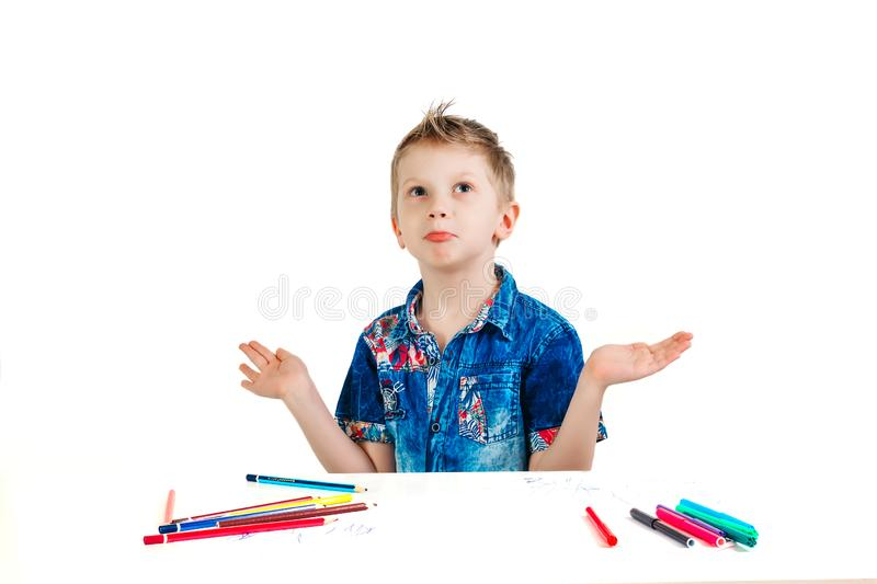 A boy of 6 years in a blue shirt makes a gesture on a white background isolate. The concept is not innocent, does not know.  royalty free stock photos