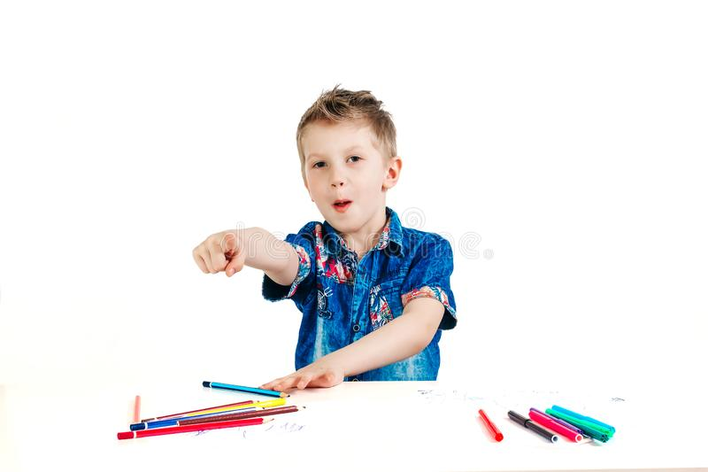 A boy of 6 years in a blue shirt is tapping his finger on a white background of isolates. The concept of farsightedness, foresight.  royalty free stock images