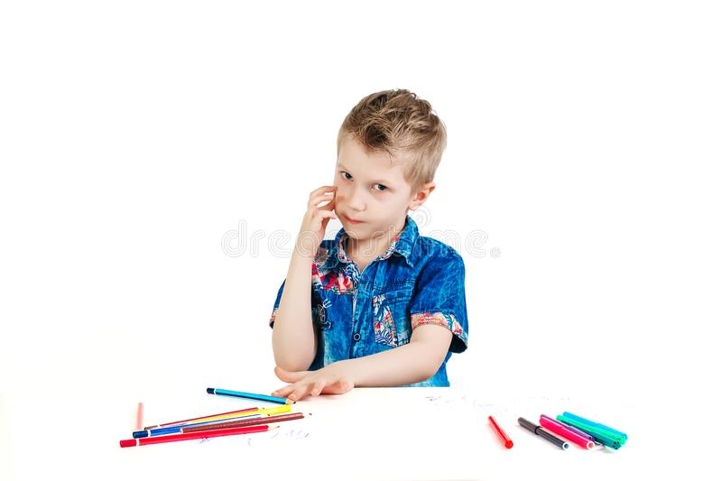 A boy of 6 years in a blue shirt thought for a white background isolate. The concept of farsightedness, foresight, a new idea.  stock photo