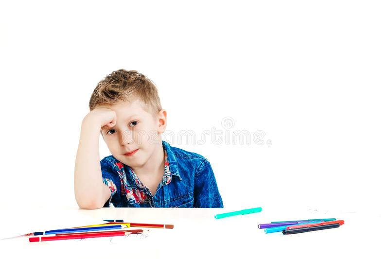 A boy of 6 years in a blue shirt thought for a white background isolate. The concept of farsightedness, foresight, a new idea.  royalty free stock images