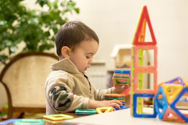 The boy 2 years building a tower from a bright and colorful designer. Intellectual toys. stock photo