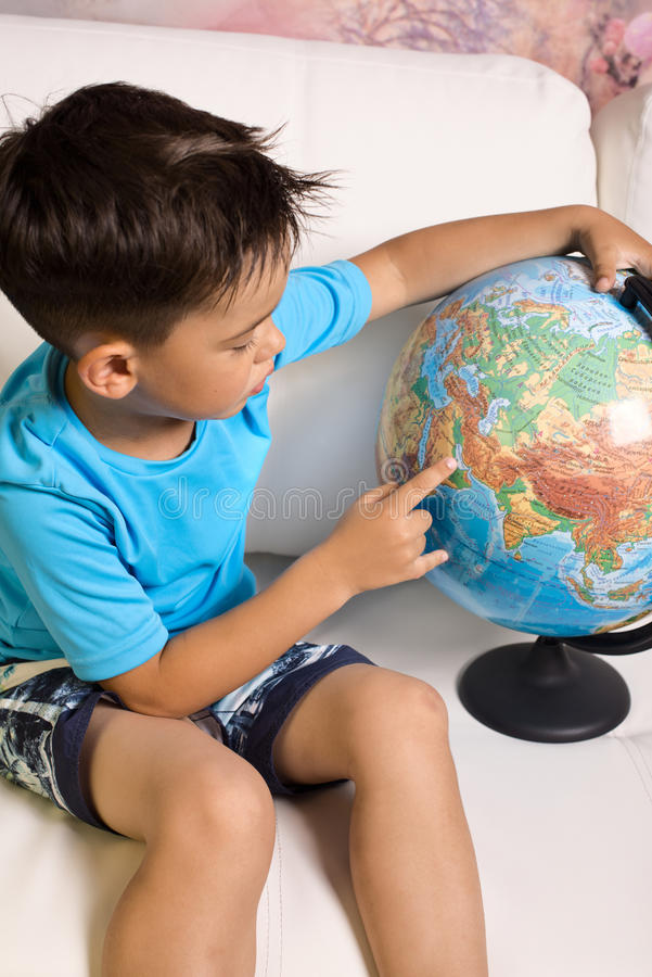 A boy of 5-6 years with a globe royalty free stock images