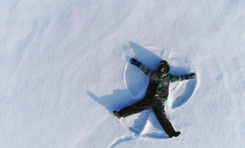 Boy of 7 years makes snow angel in snow area. Aerial foto. Boy of 7 years makes snow angel in snow area royalty free stock photos