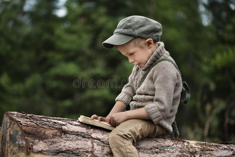 The boy, 5 years old, looks like a trapper, wanderer, lumberjack. Hut, shelter in the forest among logs of wood. A lonely walk, rest after work. Survival royalty free stock images