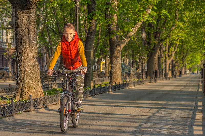 A boy of 8 years old in an orange vest rides a bicycle in a city park on a sunny spring morning stock photography