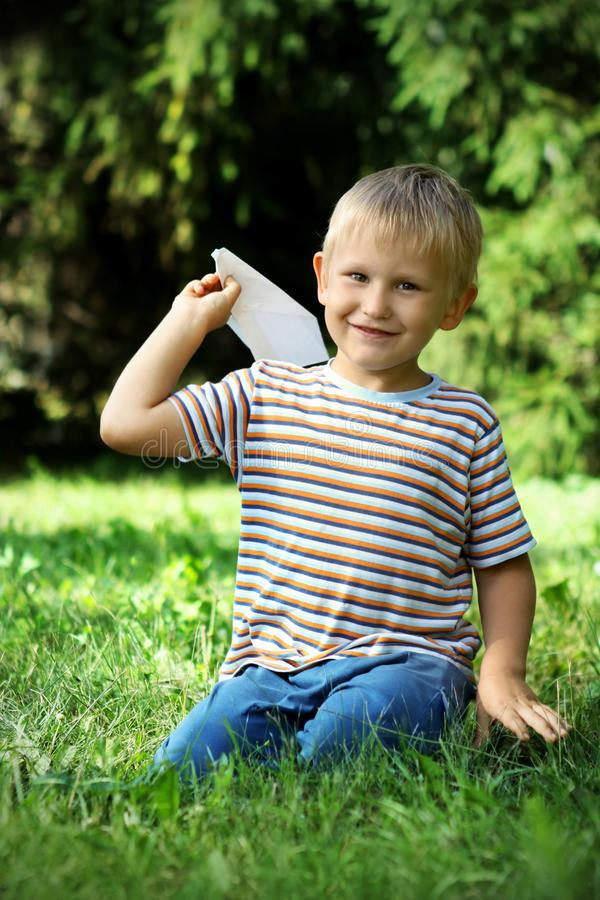 A boy of 7 years old is sitting on the grass with a paper plane in his hand. Sunny summer day. Bokeh royalty free stock photo