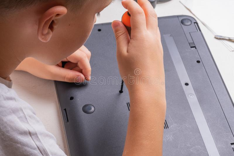 A boy of 10 years old is sorting a laptop for cleaning and maintenance. Selective focus. Screwdrivers, purge cylinder, magnifying royalty free stock image