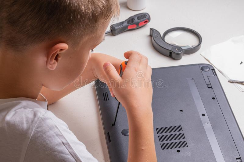 A boy of 10 years old is sorting a laptop for cleaning and maintenance. Selective focus. Screwdrivers, purge cylinder, magnifying stock photography