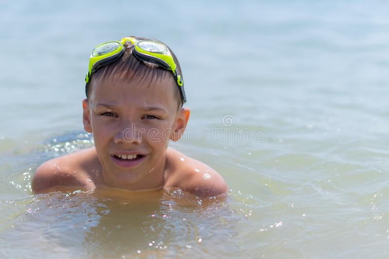 A boy of 10 years old is swimming in the sea on a clear sunny day. Child, happy, smiling, people, smile, male, happiness, kid, person, adult, lifestyle royalty free stock photo