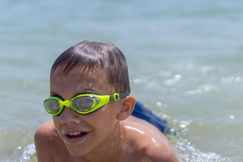 A boy of 10 years old is swimming in the sea on a clear sunny day. Child, happy, smiling, people, smile, male, happiness, kid, person, adult, lifestyle royalty free stock photos