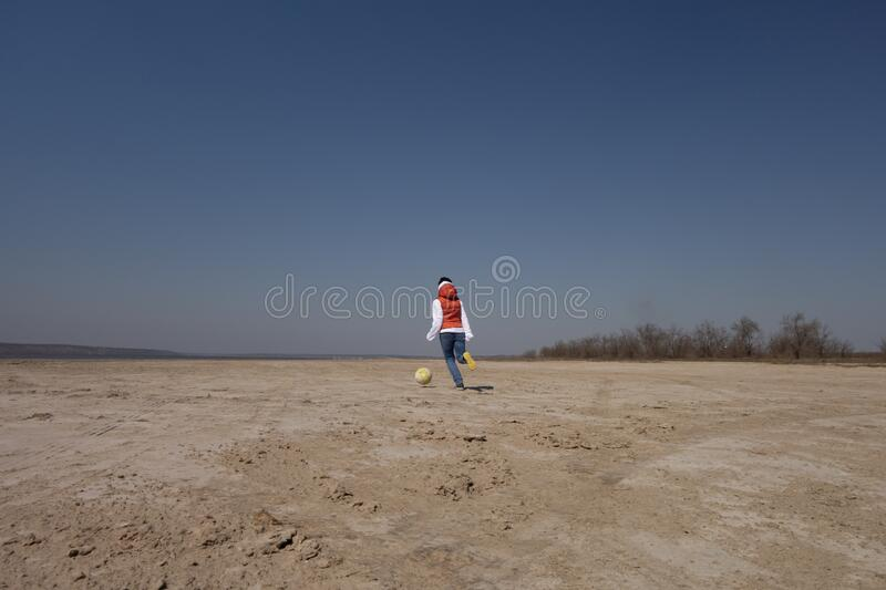 A boy of 10 years old in a white sweatshirt and orange vest plays football on a deserted beach in solitude royalty free stock images