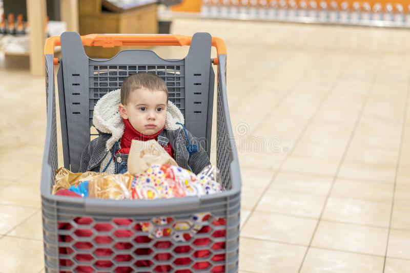 Boy 2 years in a supermarket, sitting in a cart full of various products.  royalty free stock photo