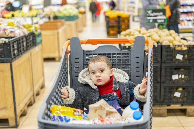 Boy 2 years in a supermarket, sitting in a cart full of various products.  stock photos
