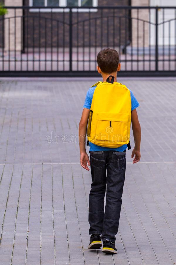 Boy with yellow backpack outdoors. Back view. Boy with yellow backpack walking outdoors. Back view stock images