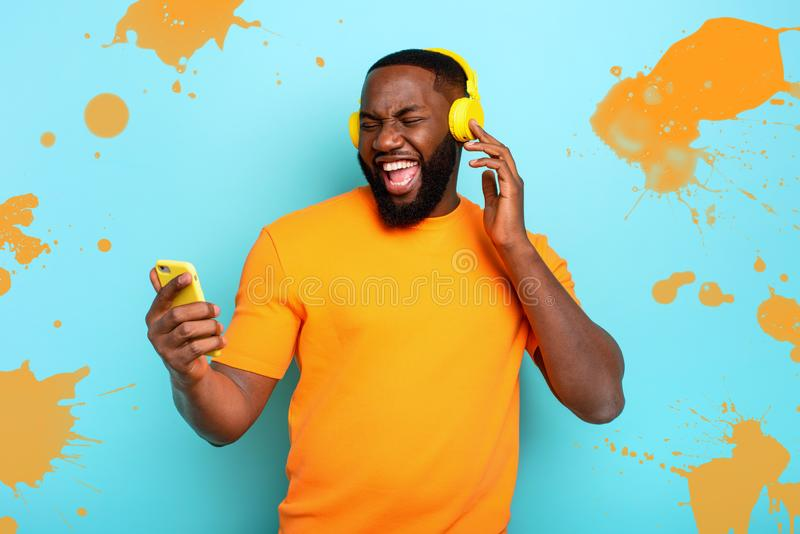 Boy with yellow headset listens to music and dances. emotional and energetic expression royalty free stock images