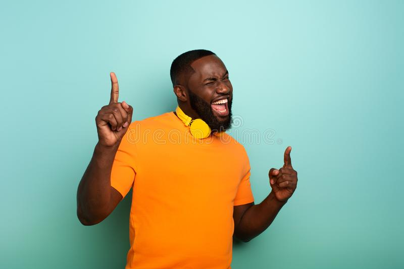 Boy with yellow headset listens to music and dances. emotional and energetic expression. Black Boy with yellow headset listens to music and dances. emotional and stock image
